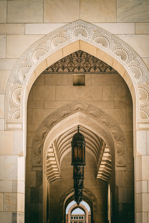 architrave: Low angle view of beautiful arab entryway with patterned motifs and a row of hanging lanterns Stock Photo