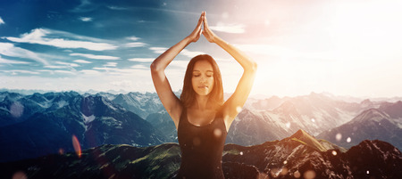 Calm beautiful woman in yoga meditation pose in front of bright mountain sunset scene with copy space