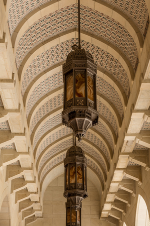 Low angle view of arched tessellated ceiling with row of ornate hanging lanterns