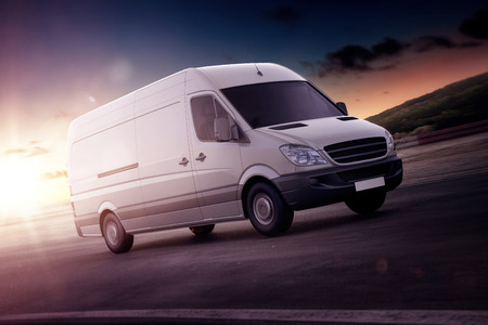 White van for freight haulage speeding along on a freeway backlit by the setting sun in a close up rendering or illustration with copy space Archivio Fotografico