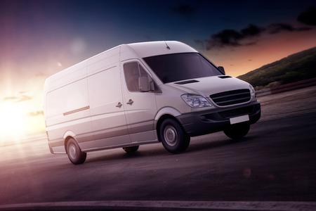 Witte bestelwagen voor vrachtvervoer versnellen op een snelweg met achtergrondverlichting door de ondergaande zon in een close-up weergave of illustratie met kopie ruimte Stockfoto - 65800179