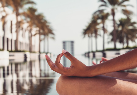 palm lined: Young woman meditating at a tropical resort sitting at the edge of a palm tree lined tranquil pool with a close up on her graceful hands in a wellness concept Stock Photo