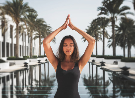 slim women: Pretty Indian woman practicing yoga on summer vacation standing meditating with closed eyes at the end of a long tranquil resort pool lined with tropical palms in a healthy lifestyle or travel concept Stock Photo