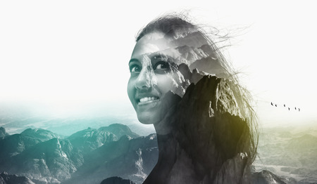 overlay: Double exposure portrait of a beautiful attractive woman and rough wild mountain scenery