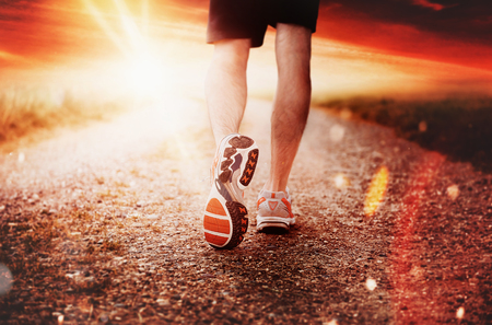 Athlete runner feet running on road closeup on shoe. Man fitness early morning sunrise jog workout concept Banque d'images - 128868364
