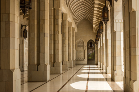 mid distance: Sun pours into beautiful empty stone corridor with arched ceilings and entry ways