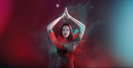 Young Indian woman practicing yoga during Holi standing meditating with hands raised in prayer against a coloful background of blended blue and red pigment or powder wafting in the air wide angle view Stock Photo