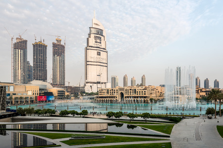 mid distance: Beautiful vacation city of Dubai with fountain beside unique skyscrapers that shape the skyline Editorial