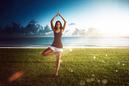 Young woman practicing yoga in a coastal field standing balancing on one leg on the green grass with a backdrop of a calm ocean and hot summer sun with lens flare