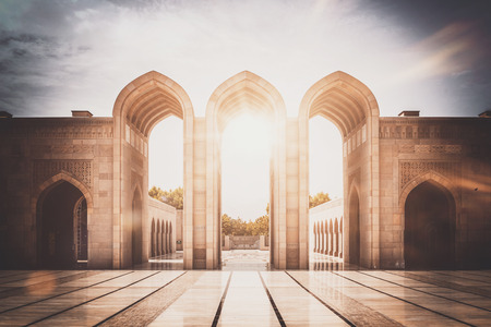 muscat: Inspirational image of stone arched entry way with reflective courtyard as the glaring sun shines behind it Stock Photo
