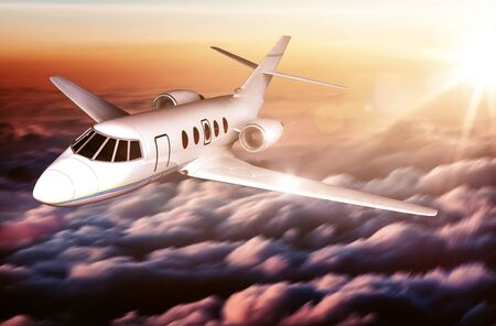 corporate jet: White unmarked executive corporate jet flying above colorful clouds at sunrise or sunset with a fiery sunburst behind the plane in a travel and transport concept Stock Photo