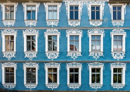 architrave: Straight on view of historic German building with blue facade and ornate windows painted white Editorial