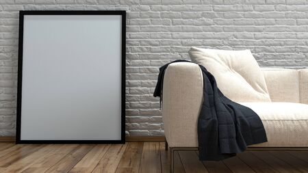 hardwood floor: Large empty simple rectangular picture frame leaning against a rough rustic white painted brick wall alongside a cream colored couch on a hardwood floor, close up 3d render Stock Photo