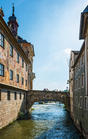 water town: Bridge over the River Regnitz in Bamberg, Bavaria, Germany with the water flowing along the historic walls of the Town Hall covered in colorful yellow frescoes