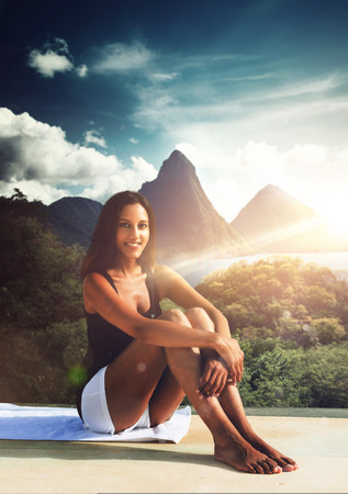 saint lucia: Barefoot young Indian woman with a happy smile relaxing on summer vacation on paving overlooking a tropical mountain landscape at sunrise backlit by the flare of the sun