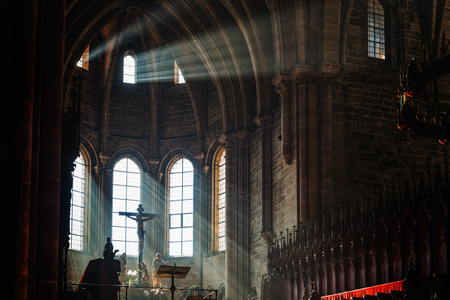 Dark church interior with crucifix above altar as light pours in from nearby arched windows