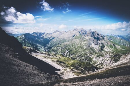 allgau: Beautiful from above on mountain valley with vignette sky near Oberstdorf, Germany. The famous Heilbronn via ferrata runs on the line. Stock Photo