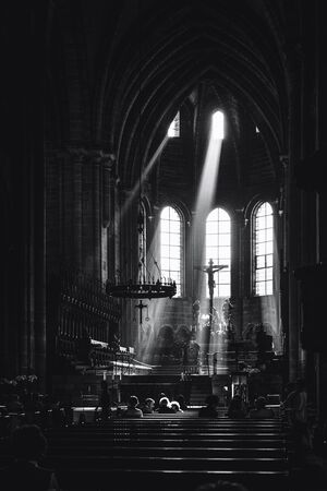 church window: Beams of light shining into the historic interior of Bamberg Cathedral illuminating the alter and crucifix with the heads of members of the congregation praying in the pews