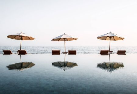 Three beach umbrellas with recliner chairs at the edge of an infinity pool overlooking a tranquil ocean at a luxury tropical resort in a travel concept