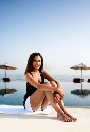 Happy relaxed young woman at a tropical resort sitting bare foot on a stone wall overlooking a seaside infinity pool with umbrellas and recliners