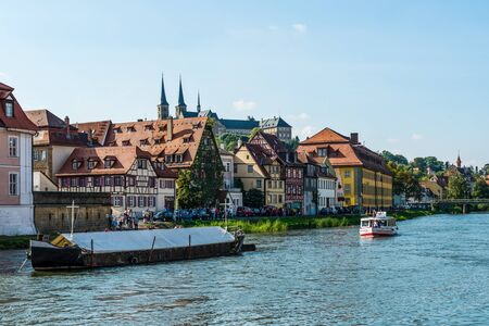 listed buildings: Boats on the River Regnitz, Bamberg, Germany sailing past the picturesque medieval buildings in this UNESCO listed World Heritage Site