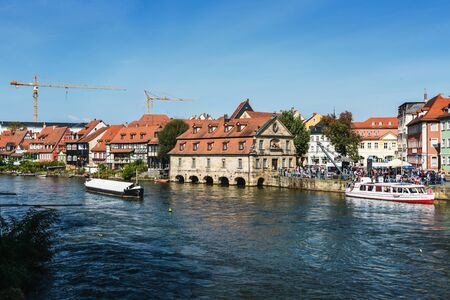 popular: Boats on the Regnitz River in Bamberg, Germany sailing past old historic houses with two industrial cranes on the horizon in the background