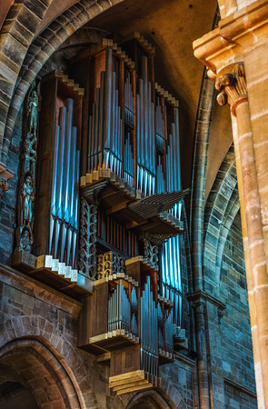 Metal organ pipes hang inside masonry of church with vaulted ceilings and arched entryways