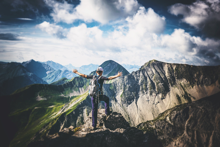 Climber celebrating his successful climb or trek standing with outspread arms on an alpine summit facing out over distant peaks and mountain ranges Stock Photo