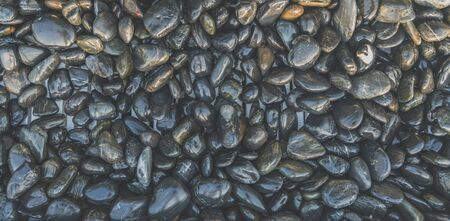 Desaturated smooth dark stones background with copy space for theme about nature and strength