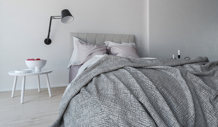 snug: Messy unmade grey bed viewed from the foot in a monochromatic gray bedroom interior with wall-mounted angle poise lamp, 3d render