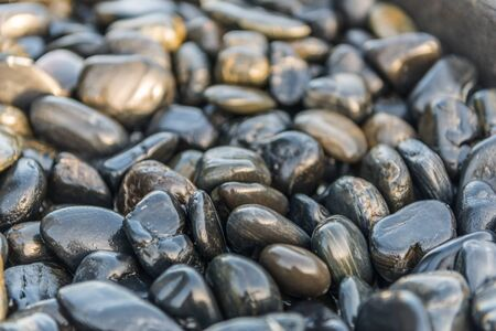 mined: Smooth gray stones with wet appearance as background about nature and man made environments