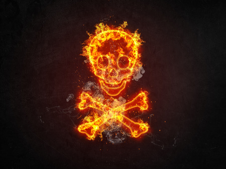 Dramatic fiery orange skull and crossbones engulfed in flames over a dark background with twinkling sparks and copy space Stock Photo
