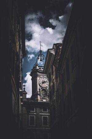 evocative: Darkened walls of buildings of old city with clock tower and bell over daylight sky with white clouds