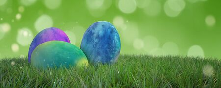 Three multicolored dyed Easter eggs on fresh green spring grass with a matching green background bokeh and copy space, panoramic banner. 3d Rendering. Stock Photo