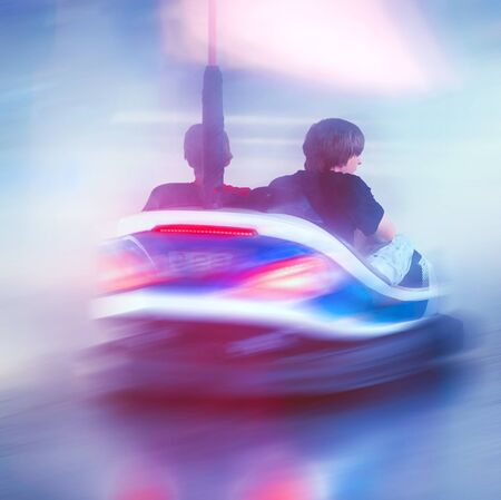 Action and motion rear view of two friends riding in brightly lit bumper car carnival ride