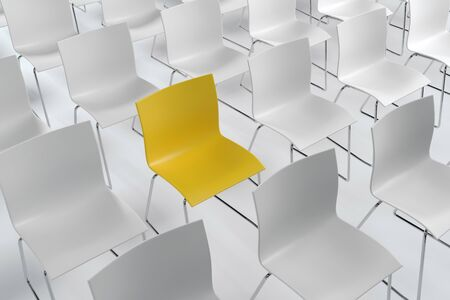 Single yellow chair in a room of white ones neatly arranged in rows for an audience in a conceptual image of standing out from the crowd. 3d rendering. Stok Fotoğraf