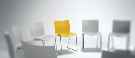 Panoramic banner of a single yellow chair in a group of blurred white ones arranged in a circle in a concept of leadership, achievement and diversity. 3d rendering.