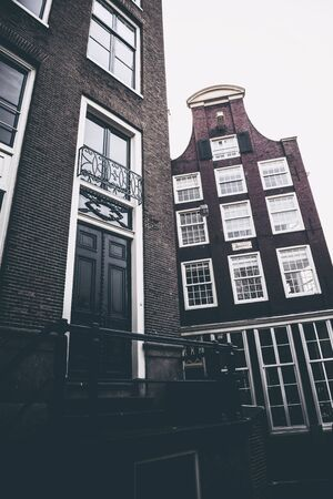 lowrise: Entrance to old bricked building next to another traditional dutch canal house with neck-gable, against grey sky - Amsterdam, Netherlands