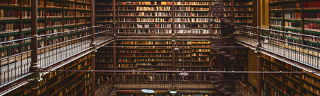 Panoramic view inside great public library with many books - The Rijksmuseum Library, Amsterdam, Netherlands