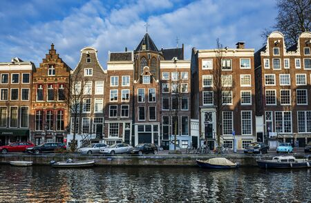 Row of historic canal houses alongside the water in Amsterdam, Netherlands with the evening sun lighting the tops of the buildings