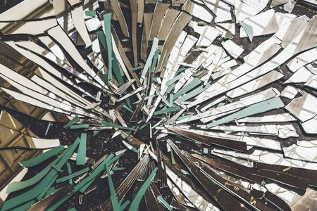 disintegrate: Close-up view of broken mirror on floor with window light and walls of old building reflected in shards