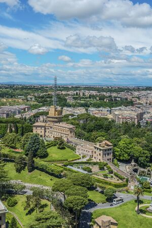 Aerial view of Vatican city of Rome. Vertical cityscape with lots of green trees and park in foreground, living buildings in distance against blue sky with clouds