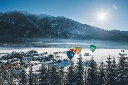 valley below: Four hot air balloons flying over an alpine resort nestling in a snowy valley below rugged mountain peaks