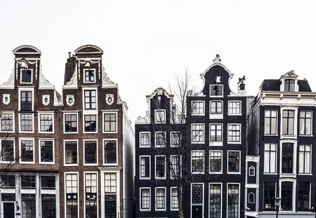 Traditional historical canal houses with neckgables on cloudy winter day, Amsterdam, Netherlands