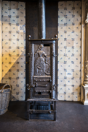 domestic: Old cast iron wood burning stove with an embossed door showing a woman in vantage clothing in an olden day tiled kitchen