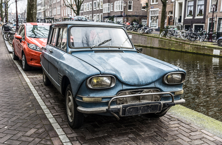 Funny curvy old blue car parked near canal in Amsterdam, Netherlands