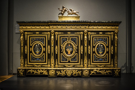Antique inlaid and ormolu Dutch cabinet decorated with vases of flowers and topped with an equestrian sculpture Editorial