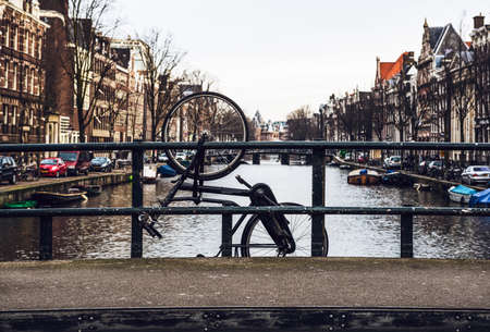traditional culture: Old broken bicycle hanging off bridge tied to railing on canal of Amsterdam, Netherlands Stock Photo