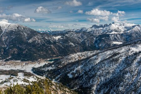 Panoramic view of Alpine mountain range in winter with cloudscape background Stock Photo