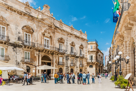 ortigia: SYRACUSE, SICILY, ITALY - APRIL 26, 2017: Tourists on main square piazza Duomo in Syracuse city in Sicily. The city is a historic town in Sicily, the capital of the province of Syracuse
